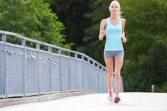 La femme court extérieur sur un pont comme formation de vigueur Photos libres de droits