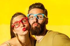 La femme couverte de taches de rousseur, et l'homme barbu envoient l'air embrassant à l'appareil-photo Photographie stock