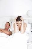 La femme couvrant ses oreilles en tant que ses maris ronfle Image stock