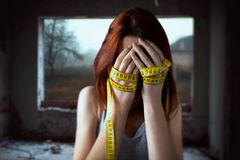 La femme couvre le visage, mains attachées avec la bande de mesure image stock