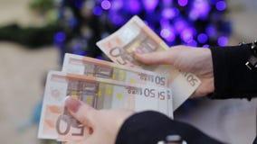 La femme croit d'euro billets de banque sur un fond de l'arbre de Noël Heure d'acheter des cadeaux banque de vidéos