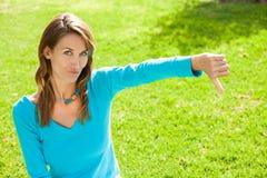 La femme déçue dans un jardin vert manient maladroitement vers le bas Photo stock