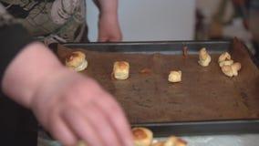 La femme décale les biscuits de finition de la plaque de cuisson à un plat clips vidéos