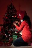 La femme décorent l'arbre de Noël dans la nuit Images stock
