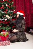 La femme décorent la maison d'arbre de Noël Photos stock