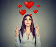 La femme désespérée dans l'amour faisant un souhait maintient ses doigts croisés Images stock