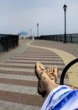 La femme détendant sur la plage, pieds en sandales se ferment  Photographie stock