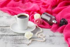 La femme détendent le temps de café avec le châle et la bouteille de parfum sur la table image stock