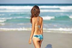 La femme détendent sur la plage et regarder à la mer Images stock