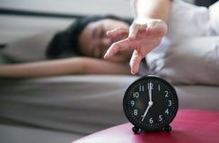 La femme déteste obtenir soumise à une contrainte réveillant le début de la matinée, femelle étirant sa main à l'alarme de sonner photo libre de droits