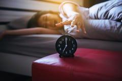 La femme déteste obtenir soumise à une contrainte réveillant le début de la matinée, femelle étirant sa main à l'alarme de sonner photographie stock