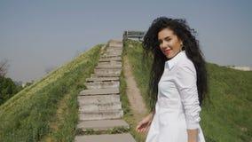 La femme d'élégance dans la longue robe blanche relève des escaliers de thee sur la colline banque de vidéos