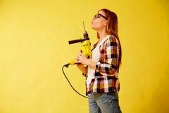 La femme d'émancipation tient habilement une perceuse, se tenant entre les boîtes studio images libres de droits