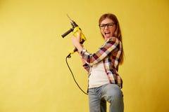 La femme d'émancipation tient habilement une perceuse, se tenant entre les boîtes studio photo libre de droits