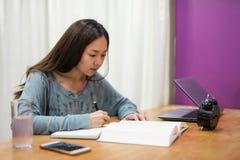 La femme d'étudiant a lu le livre et prend la note images stock