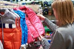 La femme d'acheteur choisit des vêtements de veste d'enfant dans le magasin Photos stock