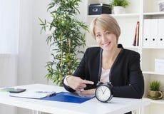 La femme d'affaires, à la table, montre l'horloge et le sourire Image stock
