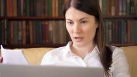 La femme d'affaires à la maison avec l'ordinateur portable ayant la causerie visuelle par l'intermédiaire du messager APP, discut clips vidéos