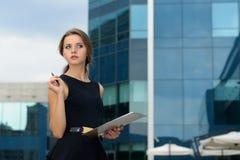 La femme d'affaires écrit dans un dossier avec des documents image stock