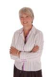 La femme d'affaires aînée de sourire avec des bras s'est pliée Photos stock