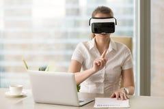 La femme d'affaires agit l'un sur l'autre avec la réalité virtuelle dans le casque de VR photographie stock libre de droits