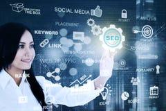 La femme d'affaires asiatique appuie sur le bouton de SEO Image stock