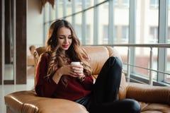 La femme d'affaires attirante dans un chandail rouge ont une pause-café photo stock
