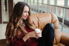 La femme d'affaires attirante ont une pause-café sur le sofa photographie stock libre de droits
