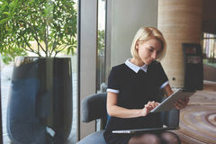 La femme d'affaires avec le pavé tactile s'assied dans l'intérieur de luxe de restaurant pendant la coupure au travail Photographie stock