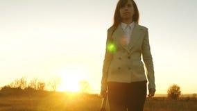 La femme d'affaires avec la valise entre dans l'éclat du coucher du soleil Mouvement lent banque de vidéos