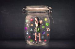 La femme d'affaires a capturé dans un pot en verre avec les icônes colorées c d'APP Photographie stock libre de droits