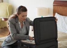 La femme d'affaires éclatent le bagage dans la chambre d'hôtel Photographie stock libre de droits