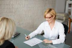 La femme d'affaires complètent une forme dans le bureau photos stock