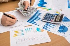 La femme d'affaires compte l'argent travail sur des graphiques de gestion photographie stock