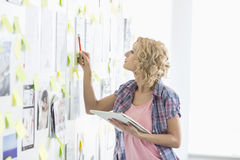 La femme d'affaires créative analysant des papiers a collé sur le mur dans le bureau photos libres de droits