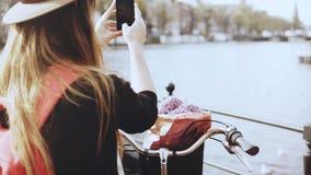 La femme d'affaires créative prend des photos sur un pont La dame élégante sur la bicyclette photographie le beau paysage de vill banque de vidéos