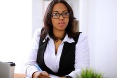 La femme d'affaires d'afro-américain est occupée avec le travail de papier dans le bureau Image stock