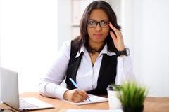 La femme d'affaires d'afro-américain est occupée avec le travail de papier dans le bureau Photographie stock libre de droits