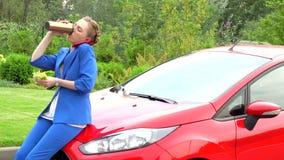 La femme d'affaires dans le costume bleu s'assied sur le capot de la voiture rouge Elle parle au téléphone et mange La fille tien clips vidéos