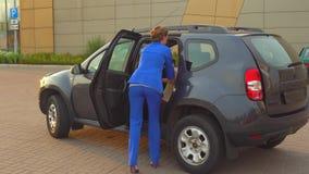 La femme d'affaires dans le costume bleu vient à la voiture et ouvre de retour la porte Elle a mis dessus des sacs de siège qu'el banque de vidéos