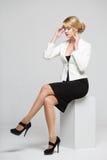 La femme d'affaires dans un costume élégant a soulevé ses mains à la tête Photos stock