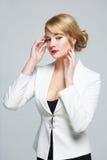 La femme d'affaires dans un costume élégant a soulevé ses mains à la tête Images stock