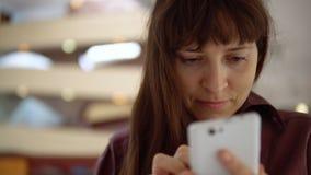La femme d'affaires de brune dans un chemisier foncé utilise un smartphone à l'intérieur banque de vidéos