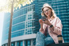 La femme d'affaires de hippie en verres s'assied dehors et utilise le smartphone Est tout près la tasse de café À l'arrière-plan  Image stock