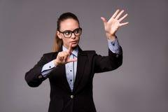 La femme d'affaires de jeune femme appuyant sur les boutons virtuels Image stock