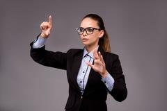 La femme d'affaires de jeune femme appuyant sur les boutons virtuels Photo stock