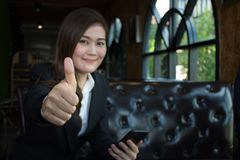 La femme d'affaires de sourire heureuse avec des pouces lèvent le geste regardant l'appareil-photo se reposant sur un sofa photo stock