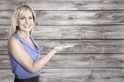 La femme d'affaires de sourire plus de wodden se présenter de fond Photographie stock libre de droits