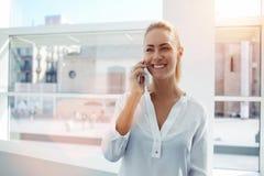 La femme d'affaires de sourire s'est habillée dans le tenue de soirée ayant la conversation agréable sur le mobile photographie stock