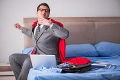 La femme d'affaires de superhéros travaillant dans le lit Photographie stock libre de droits